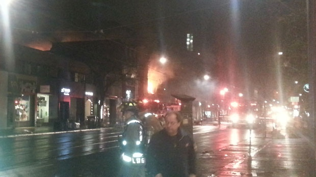 Flames are seen shooting out of a commercial building on Queen Street West at Soho Street. (Sandie Benitah/CP24.com)