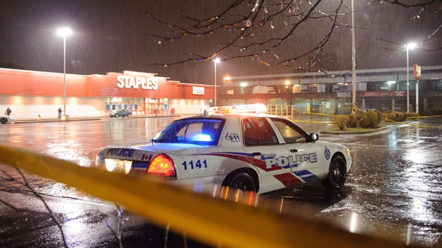 Toronto Police sit at a taped off Staples outlet parking lot after strong storm winds caused a piece of a sign to fall, killing one, in Toronto on Oct. 29, 2012. (The Canadian Press/Victor Biro)