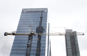 The CN tower is reflected in a high rise building behind a construction crane in downtown Toronto on Saturday, February 4, 2012. (THE CANADIAN PRESS/Pawel Dwulit)