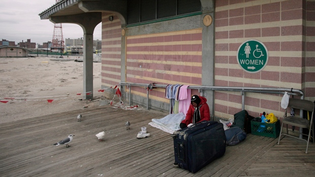A homeless woman sits on the Coney Island boardwalk in New York on Wednesday, Nov. 7, 2012, as anothe storm approaches a week after the region was hit by superstorm Sandy. (AP Photo/Mark Lennihan)