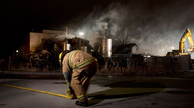 An emergency worker rolls up a hose outside Neptune Technologies and Bio Resources in Sherbrooke, Que., on Thursday, Nov. 8, 2012. (The Canadian Press/Graham Hughes)