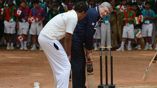 Prime Minister Stephen Harper takes part in a cricket lesson as he visits the Bishop Cotton Boys and Girls School in Bangalore, India on Friday, Nov. 9, 2012. (The Canadian Press/Sean Kilpatrick)