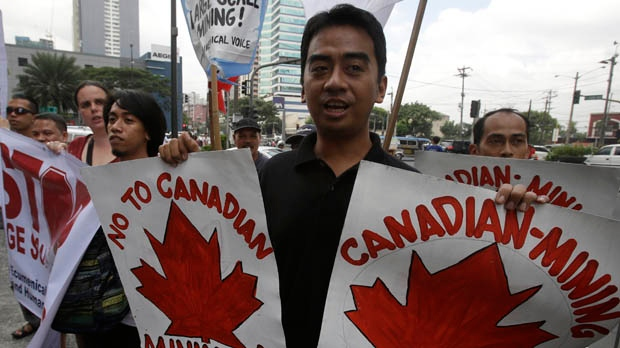 Protesters display placards as they picket the Canadian Embassy to coincide with the official visit of Canadian Prime Minister Stephen Harper in the financial district of Makati, Philippines, on Friday, Nov. 9, 2012. (AP Photo/Bullit Marquez)
