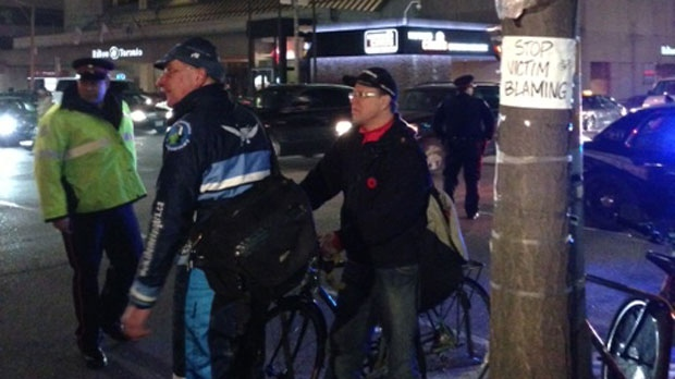 Cyclists and a Toronto police officer are seen in this photo at a a demonstration at University Avenue and Richmond Street on Friday, Nov. 9, 2012. (CP24/Cristina Tenaglia)