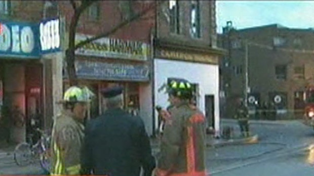 Fire officials stand at the scene of a blaze on Queen Street West, just west of Spadina Avenue, on Monday, Nov. 12, 2012.