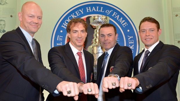 Hockey Hall of Fame inductees, from left, Mats Sundin, Joe Sakic, Adam Oates and Pavel Bure pose for a photograph with their rings at the Hockey Hall of Fame in Toronto, Monday, Nov. 12, 2012. (AP Photo/The Canadian Press, Nathan Denette)