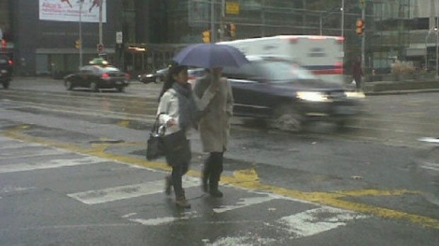 People walk in the rain at University Avenue and Queen Street West on Monday, Nov. 12, 2012. (Chris Kitching/CP24)