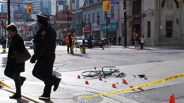 A police officer escorts a woman from the scene of a garbage truck-bicycle collision that seriously injured a woman at Yonge and Gerrard streets on Tuesday Nov. 13, 2012. (The Canadian Press/Colin Perkel)