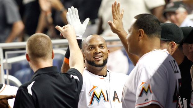 Miami Marlins Emilio Bonifacio, center, is congratulated by teammates after hitting a home run in the second inning of a baseball game against the Atlanta Braves on Monday, July 23, 2012 in Miami. (AP Photo/Terry Renna)