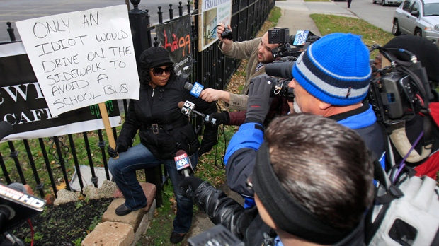 Shena Hardin talks to the media as she holds up a sign while serving a highly-public sentence in Cleveland on Wednesday, Nov. 14, 2012. Hardin drove on a sidewalk to avoid a school bus that was unloading children. (AP Photo/Tony Dejak)