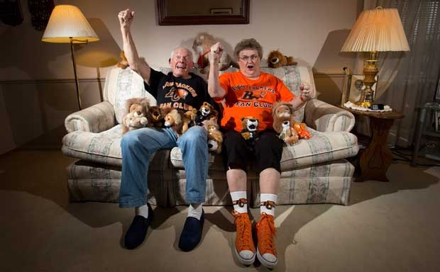 B.C. Lions' fans Ray Brittain, left, and his wife Jenny pose for a photograph at their home in New Westminster, B.C., on Monday November 12, 2012. Regardless of whether their home team is in the final, CFL fans are universally game for a celebration come Grey Cup time. (Darryl Dyck/The Canadian Press)