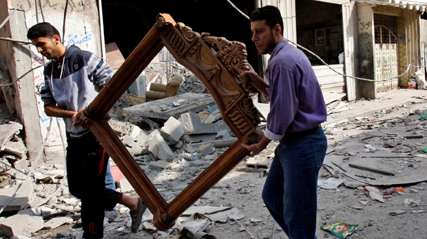 Palestinians carry a frame from the destroyed house of Islamic Jihad militant Hasam Al Kholy, which was hit overnight in an Israeli strike on Gaza City on Tuesday, Nov. 20, 2012. (AP Photo/Adel Hana)