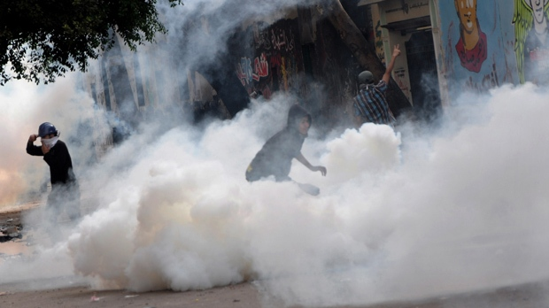 Egyptian protesters throw back tear gas canisters during clashes with security forces near Tahrir Square in Cairo, Egypt on Wednesday, Nov. 21, 2012. (AP Photo/Mohammed Asad)