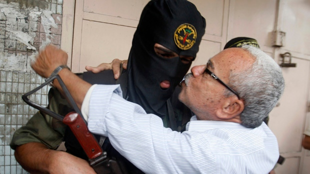 A Gaza resident hugs a Palestinian Islamic Jihad militant after a press conference in Gaza City on Thursday, Nov. 22, 2012. (AP Photo/Hatem Moussa)