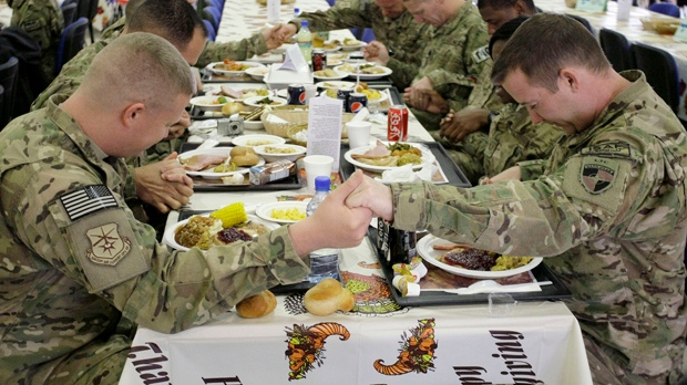 U.S. soldiers pray before eating a Thanksgiving meal at a dining hall at the U.S.-led coalition base in Kabul, Afghanistan on Thursday, Nov. 22, 2012. (AP Photo/Musadeq Sadeq)