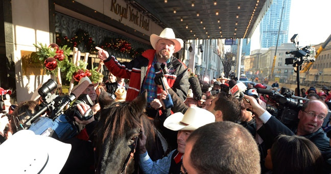Reporters and photographers surround a Calgary Stampeder rider and horse outside the Royal York Hotel in Toronto on Thursday Nov. 22, 2012. By tradition, the Stampeders try to sneak a horse in a hotel when the team vies for the Grey Cup. THE CANADIAN PRESS/Ryan Remiorz