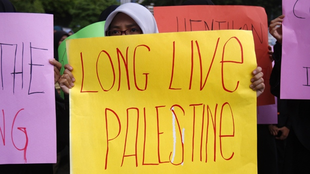 A woman holds a placard during a protest against Israel's operations in Gaza Strip in front of the U.S. Embassy in Kuala Lumpur, Malaysia on Friday, Nov. 23, 2012. (AP Photo/Lai Seng Sin)