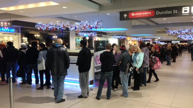 People line up for a free $10 gift card at the guest services desk at Toronto's Eaton Centre during a Black Friday sales promotion early Friday, Nov. 23, 2012. (Cam Woolley/CP24)