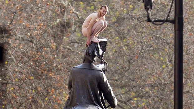 A naked man sits on top of a statue of George, Duke of Cambridge, in London on Friday Nov. 23, 2012. (AP Photo/ John Stillwell/PA)
