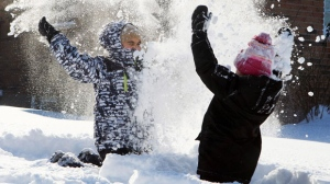 Children play in the fresh snow in London, Ontario, on Tuesday, Jan. 3, 2012. (The Canadian Press/Dave Chidley)