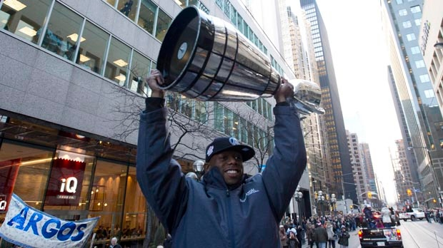 Toronto Argonauts player Jordan Younger hoists the Grey Cup during a victory parade in Toronto on Tuesday, Nov. 27, 2012. (The Canadian Press/Nathan Denette)