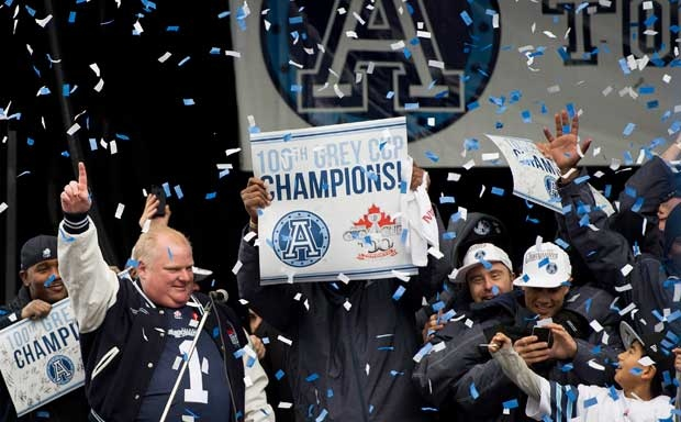 Toronto Mayor Rob Ford, left, speaks on stage with Toronto Argonauts players while celebrating the team's Grey Cup victory in downtown Toronto on Tuesday, Nov.27, 2012. (Nathan Denette/The Canadian Press)