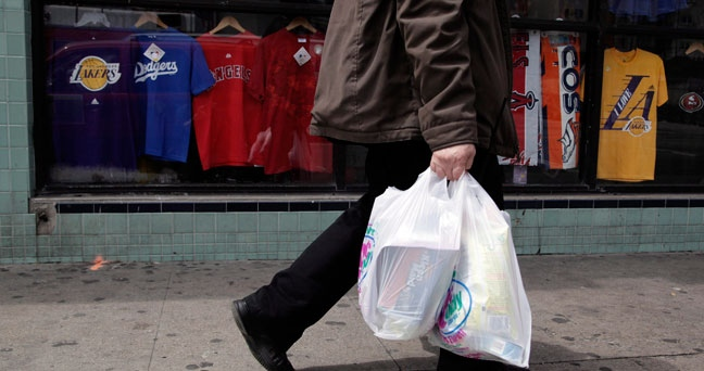 A man walks along the street with plastic bags in Los Angeles, Thursday, May 24, 2012. Toronto city council has voted not to implement a bylaw that would have banned plastic bags as of January 1. (AP Photo/Jae C. Hong)