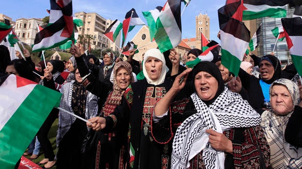 Palestinian refugee women chant slogans and wave Palestinian flags during a rally supporting the Palestinian UN bid for observer state status in front the United Nations headquarters in Beirut, Lebanon on Thursday, Nov. 29, 2012. (AP Photo/Bilal Hussein)