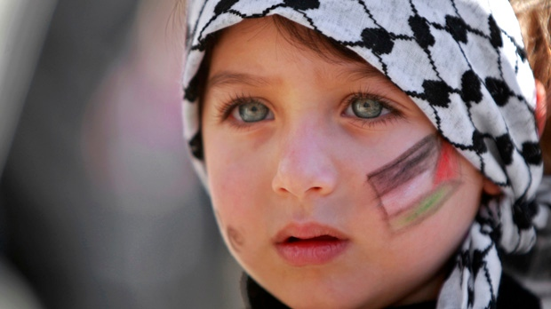 A girl with the Palestinian flag painted on her face attends a rally supporting the Palestinian UN bid for observer state status in Ramallah on Thursday, Nov. 29, 2012. (AP Photo/Majdi Mohammed)