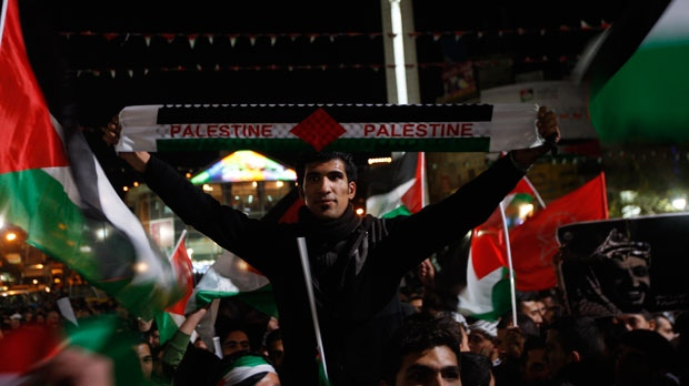 Palestinians wave Palestinian flags as they watch a large screen showing the UN General Assembly vote in the west bank city of Ramallah on Thursday, Nov. 29, 2012. (AP Photo/Majdi Mohammed)