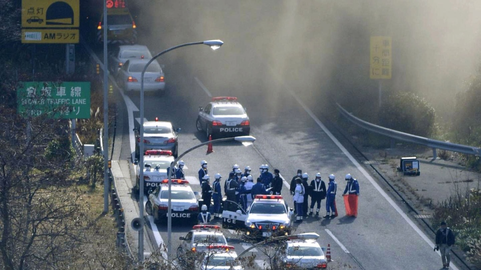 Police vehicles are parked at the entrance as smoke billows out of the Sasago Tunnel on the Chuo Expressway in Koshu, Yamanashi Prefecture, central Japan, Sunday morning, Dec. 2, 2012. (AP /Kyodo News)