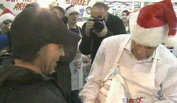 David Mirvish (right) hands a turkey to Mariano Cordeiro, the first in line for Honest Ed's annual turkey giveaway. The store gave away 1,200 turkeys Sunday as an annual holiday tradition continued.