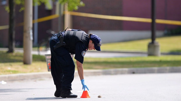 A police officer places a marker on Danzig Street in Toronto on July 17, 2012. (The Canadian Press/Aaron Vincent Elkaim)