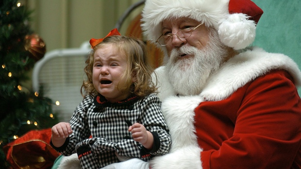 Child cries on lap of mall Santa Claus