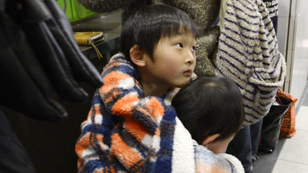 Children cuddle each other while they and their mother are stranded at a railway station in Sendai, Japan on Friday, Dec. 7, 2012, after trains were halted following a strong earthquake that struck off the coast of northeastern Japan. (AP Photo/Kyodo News)