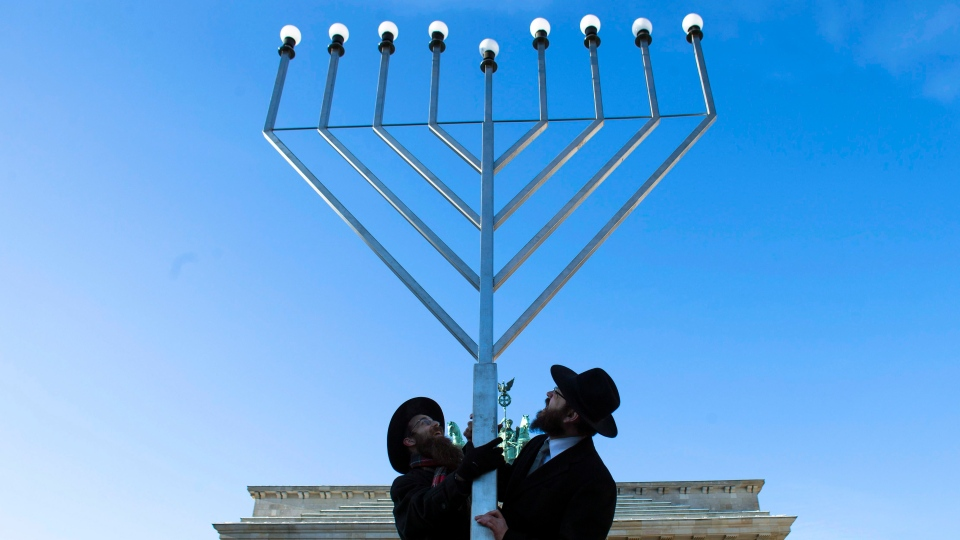 Rabbi Yehuda Teichtal, right, and Rabbi Segal Shmoel, left, install a giant Hanukkah Menorah, at the Pariser Platz in front of the Brandeburg Gate in Berlin, Friday, Dec. 7, 2012. The eight day Jewish Festival of Lights, Hanukkah will start on Dec. 8. (AP /Markus Schreiber)