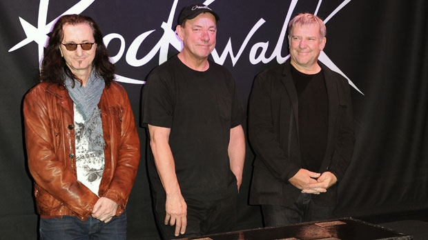 This Nov. 20, 2012 file photo shows members of the band Rush, from left, Geddy Lee, Neil Peart, and Alex Lifeson at the RockWalk induction of Rush at Guitar Center in Los Angeles. (Photo by Richard Shotwell/Invision/AP)