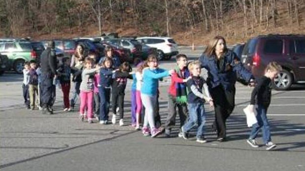 In this photo provided by the Newtown Bee, Connecticut State Police lead children from the Sandy Hook Elementary School in Newtown, Conn., following a reported shooting there Friday, Dec. 14, 2012. (AP /Newtown Bee, Shannon Hicks)