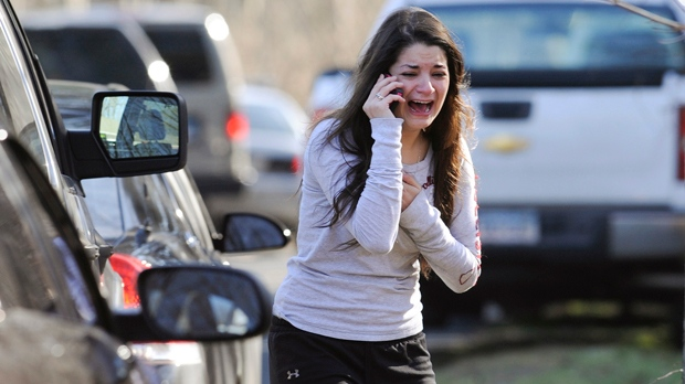 A woman waits to hear about her sister, a teacher, after a shooting at the Sandy Hook Elementary School in Newtown, Conn., on Friday, Dec. 14, 2012. (AP Photo/Jessica Hill)