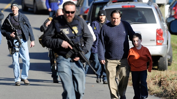 Parents leave a staging area after being reunited with their children following a shooting at the Sandy Hook Elementary School in Newtown, Conn., on Friday, Dec. 14, 2012. (AP Photo/Jessica Hill)
