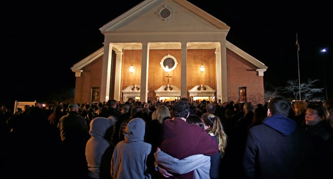 As hundreds stand outside St. Rose of Lima Roman Catholic Church, which was filled to capacity, a couple embrace during a healing service held in for victims of an elementary school shooting in Newtown, Conn., Friday, Dec. 14, 2012. (AP / Charles Krupa)