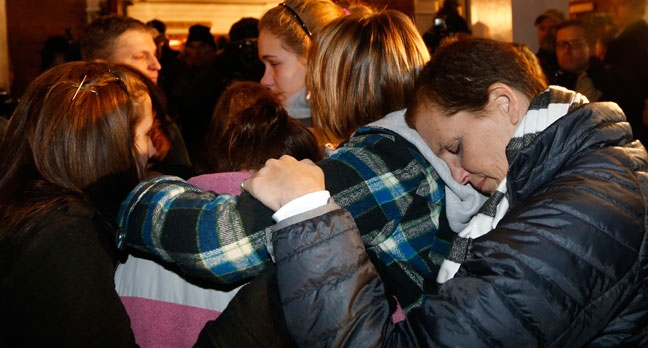 Girls embraces outside St. Rose of Lima Roman Catholic Church, which was filled to capacity, during a healing service held in for victims of an elementary school shooting in Newtown, Conn., Friday, Dec. 14, 2012. A gunman opened fire at Sandy Hook Elementary School in Newtown, killing 26 people, including 20 children. (AP Photo/Charles Krupa)