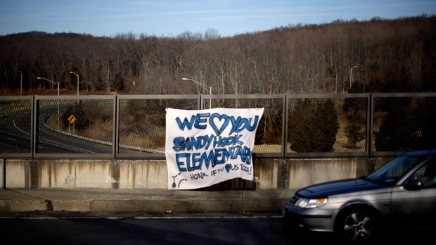 A banners hangs from an overpass encouraging passing motorists to honk their horns in support of the Sandy Hook Elementary School shooting victims on Saturday, Dec. 15, 2012, in Newtown, Conn. (AP Photo/David Goldman)