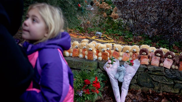 Ava Staiti, 7, of New Milford, Conn., looks up at her mother Emily Staiti, while visiting a sidewalk memorial with 26 teddy bears, each representing a victim of the Sandy Hook Elementary School shooting on Sunday, Dec. 16, 2012, in Newtown, Conn. (AP Photo/David Goldman)