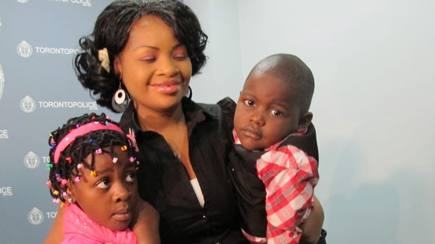 Beatra Muzabazi is seen with her daughter Rene, 7, and son Shane, 4, at police headquarters in Toronto on Monday, Dec. 17, 2012. (The Canadian Press/Colin Perkel)