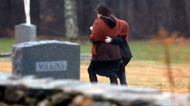 Veronique Pozner, left, embraces a young girl as she arrives at B'nai Israel Cemetery for burial services for her six-year-old son Noah Pozner on Monday, Dec. 17, 2012, in Monroe, Conn. (AP Photo/Julio Cortez)