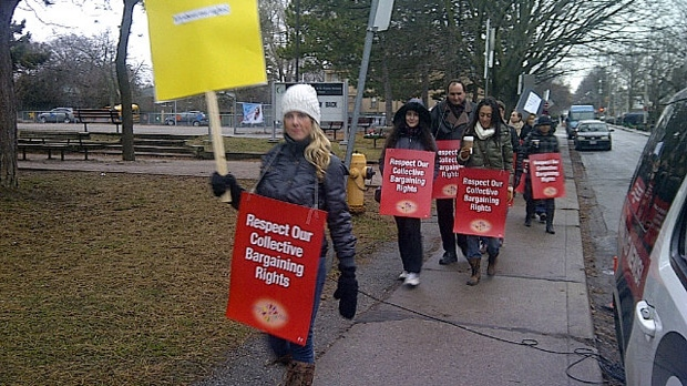 Elementary school teachers walk a picket line outside Duke of Connaught Junior and Senior Public School in Toronto on Tuesday, Dec. 18, 2012. (Rena Heer/CP24)