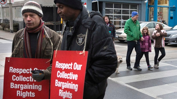 Children walk past striking teachers as they stand on a picket line in Toronto on Tuesday, Dec. 18, 2012. (The Canadian Press/Chris Young)
