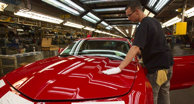 In this Friday, June 10, 2011, photo, a worker checks the paint on a Camaro at the GM factory in Oshawa, Ontario. (AP Photo/The Canadian Press, Frank Gunn)