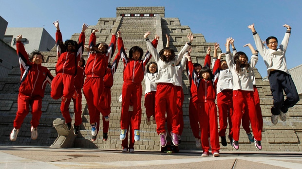 Students jump together as they pose for photographers in front of a mock pyramid after the countdown time when many believed the Mayan people predicted the end of the world on Friday, Dec. 21, 2012, in Taichung, Taiwan. (AP Photo/Wally Santana)